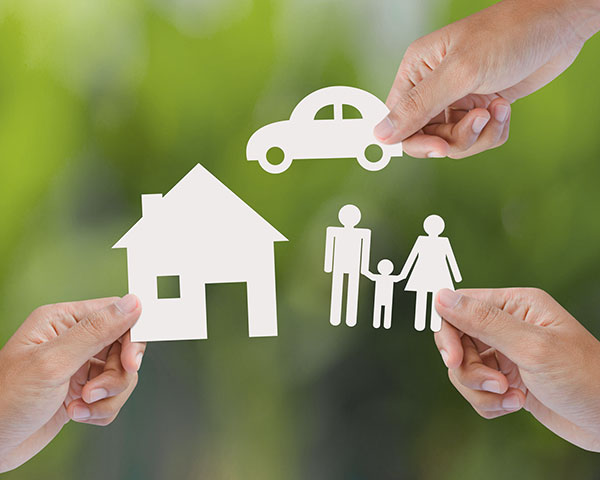 Paper cutouts of a home, car, and family